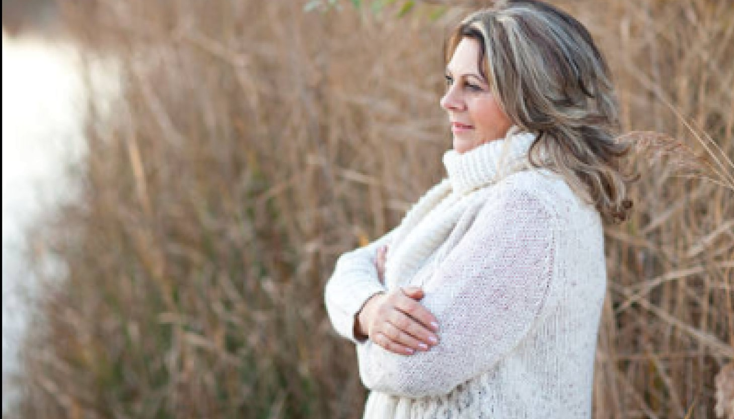 Woman standing by rivers edge with arms folded with a sense of improved life quality after receiving treatment for menopause.