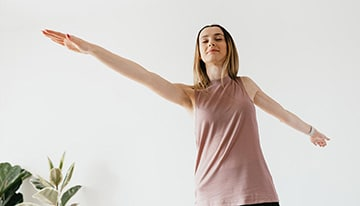 Woman with outstretched arms on her own lotus journey with the support of women's health services.